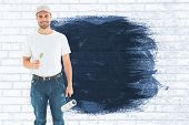 foto of knee-cap  - Happy man holding paint roller and paintbrush against white wall - JPG