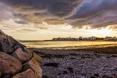 stock photo of galway  - beach in Galway Bay at sunset with rocks and clouds - JPG