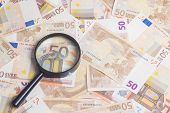 foto of fifties  - Closeup of fifty euro notes through magnifer background - JPG