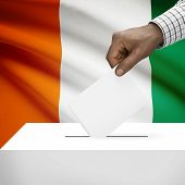 stock photo of ivory  - Ballot box with flag on background  - JPG