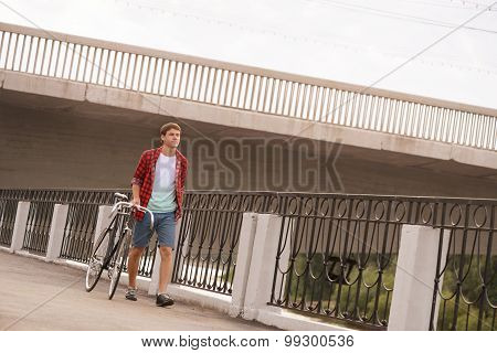 Hipster man with bicycle walking on the quay