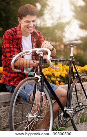 Handsome, happy man with his bicycle Sitting on flowerbed withal yellow flowers.