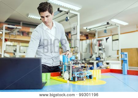 Electrical Engineer Programming A Robot During Robotics Class