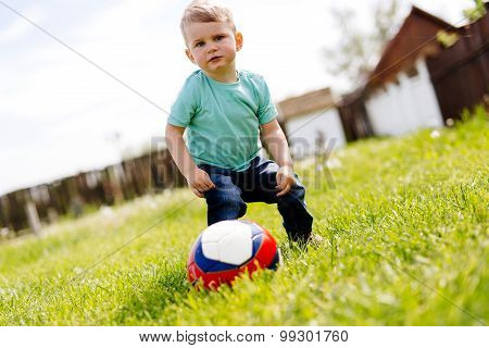 Adorable Small Boy Playing With A Soccer Ball Outdoors