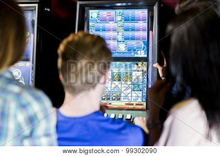 Friends Gambling In A Casino Playing Slot And Various Machines