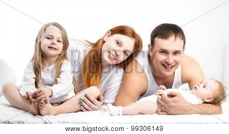 happy family: mother, father, their five years old daughter and their two months old baby in bed at home