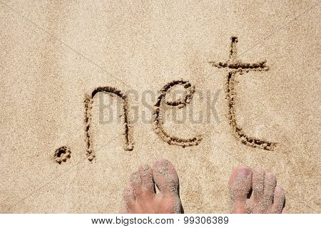 The word .net handwritten in sand on a beach, ideal for internet or conceptual designs background with feet