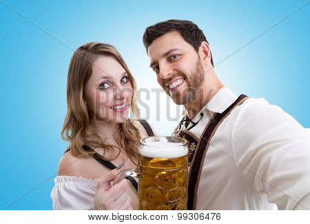 Couple in traditional bavarian costume on blue background