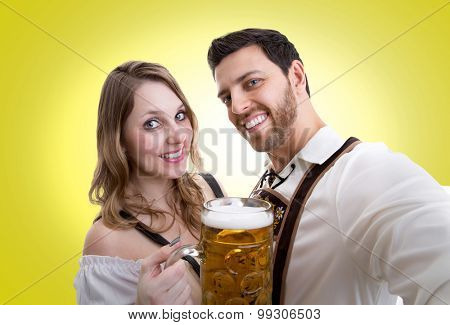 Couple in traditional bavarian costume on yellow background