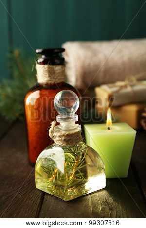 Essential oil of pine, bath salt with pine extract and spa treatments on wooden background