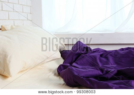 Comfortable bed with purple blanket and pillows in bedroom