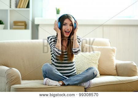 Woman listening music in headphones while sitting on sofa in room