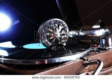 Gramophone with vinyl record on wooden table on dark background
