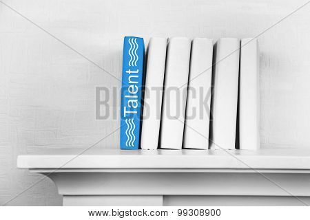 Stack of books on shelf on wall background