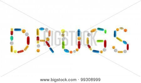 The word Drugs made with pills isolated on white