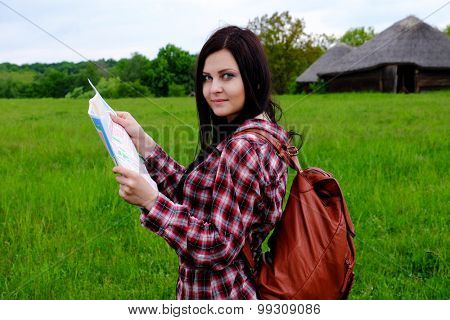Young woman tourist with backpack and map on beautiful landscape background