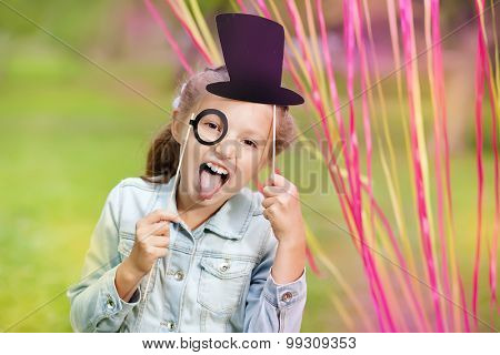 little girl with funny paper glasses and hat