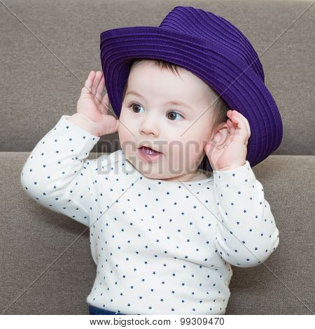 Caucasian baby boy weared a hat sitting on sofa at home