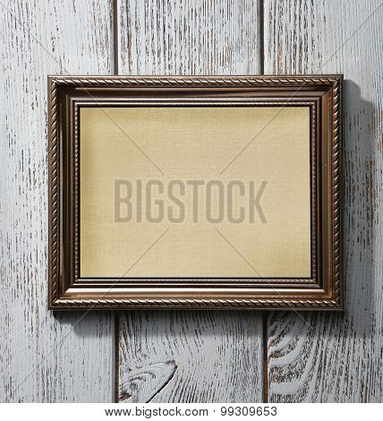 Old frame with empty canvas on wooden background