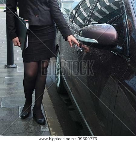 Close-up image of a business woman near a representative car