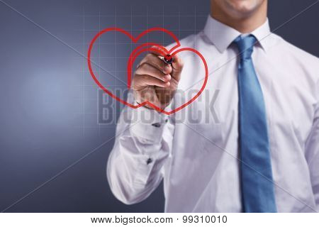 Man drawing heart on grey background
