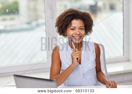 education, business and technology concept - happy african american businesswoman or student with laptop computer and pen at office