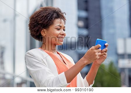 business, technology, communication and people concept - young smiling african american businesswoman with smartphone in city