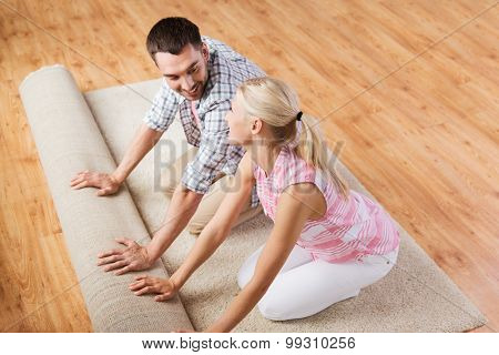 people, repair and renovation concept - happy couple unrolling carpet or rug on floor at home
