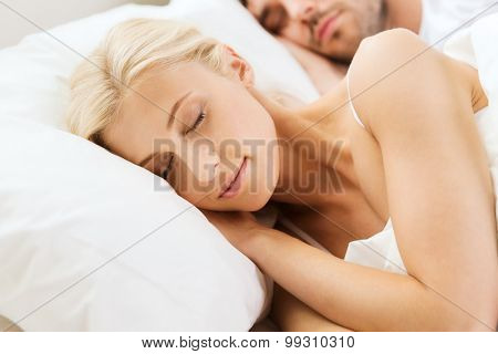 people, rest, relationships and happiness concept - happy woman and man sleeping in bed at home
