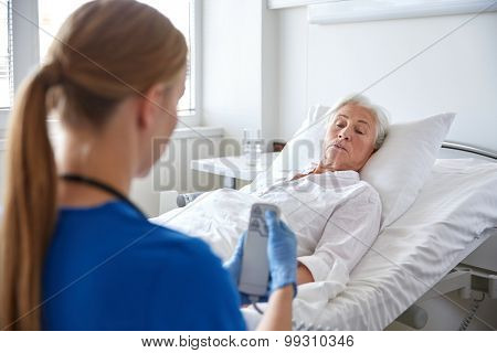 medicine, age, support, health care and people concept - doctor or nurse adjusting bed with remote control for senior woman patient at hospital ward