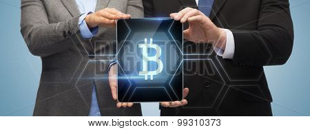 business, technology and internet concept - businessman and businesswoman with bit coin sign on tablet pc screen