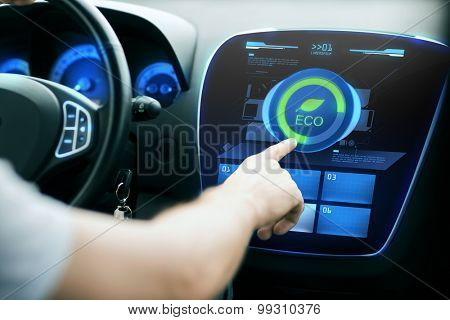transport, modern, green energy, technology and people concept - male hand using car eco system mode