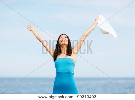 summer holidays and vacation - girl with hands up on the beach