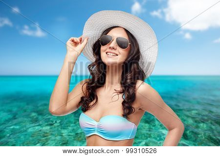 people, summer holidays, travel and tourism  concept - happy young woman in bikini swimsuit, sunglasses and sun hat over sea and blue sky background