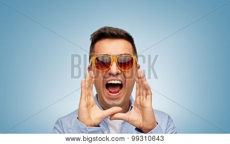 summer, emotions, communication and people concept - face of angry middle aged latin man in shirt and sunglasses over blue background