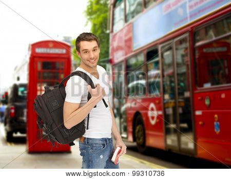 people, travel, tourism and education concept - happy young man with backpack and book over london city bus on street background