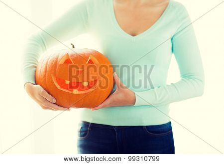 holidays, halloween, decoration and people concept - close up of woman with pumpkins at home