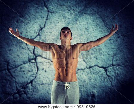 sport, bodybuilding, strength and people concept - young man standing with raised hands over concrete wall background
