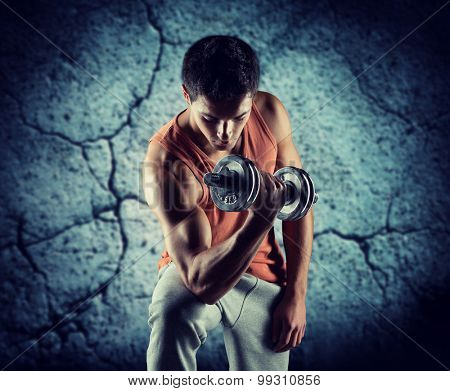 sport, bodybuilding, training and people concept - young man with dumbbell flexing biceps over concrete wall background