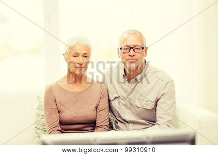 family, technology, age and people concept - senior couple watching tv at home