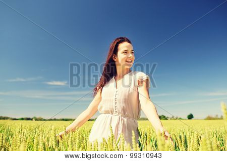 happiness, nature, summer, vacation and people concept - smiling young woman on cereal field