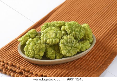 bowl of wasabi crackers on brown place mat