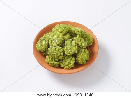 bowl of wasabi crackers on white background