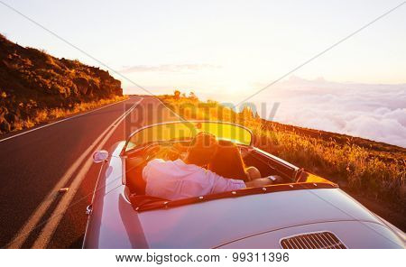 Romantic Couple Driving into the Sunset in Classic Vintage Sports Car