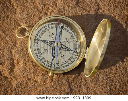 Traditional style compass on red rock