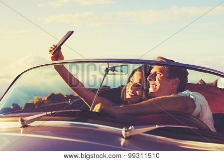Romantic Young Couple Taking a Selfie in Classic Vintage Sports Car at Sunset