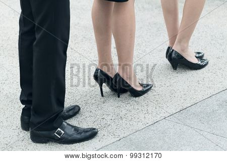 Business woman and man wait in line, closeup image with part of body.