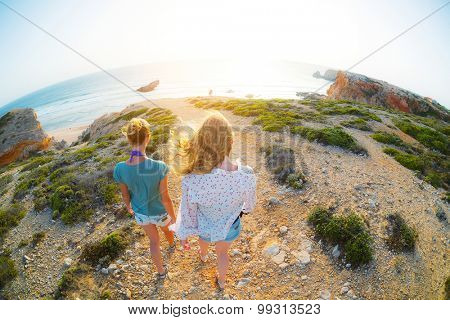 Two young ladies walking on the rocky land towards the cliff's edge and ocean