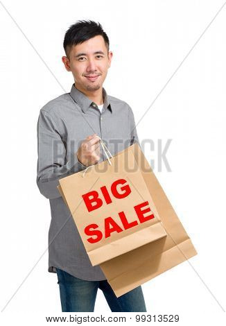 Asian man hold with shopping bag and showing big sale