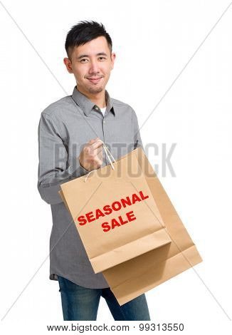 Asian man hold with shopping bag and showing seasonal sale